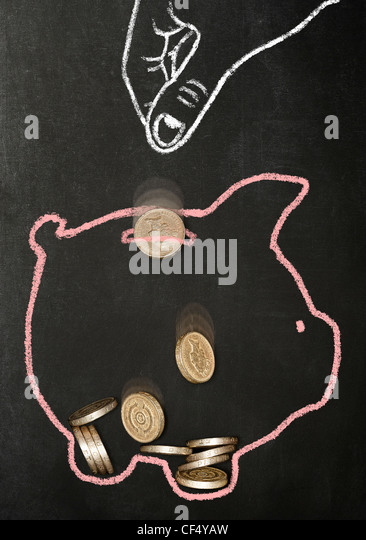 Chalk drawn hand dropping real pound coins into a chalk drawn piggy bank - Stock Image