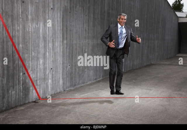 businessman standing behind red line - Stock Image