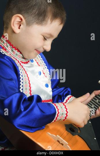 Little boy playing balalaika - Stock Image
