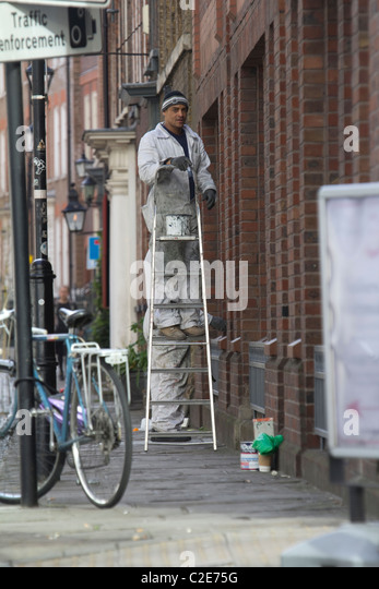 Painter decorator, on stepladder painting exterior of building in Central London - Stock Image
