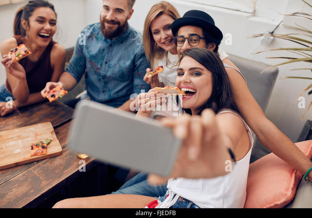 Group of multiracial young people taking a selfie while eating pizza. Young woman eating pizza her friends sitting - Stock Image