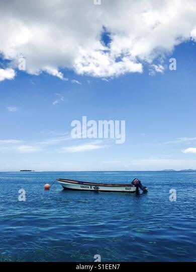 A anchored boat sits in the bay. Tavarua, Fiji. - Stock Image