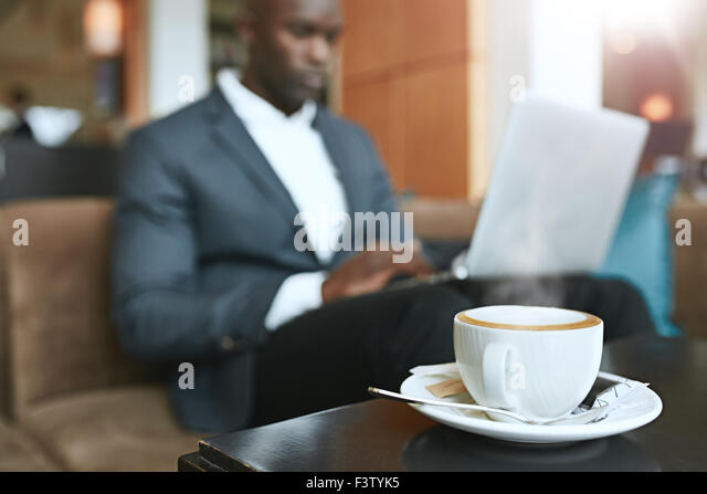 Refreshing hot cup of coffee on table with a businessman sitting in background working on laptop at hotel lobby. - Stock Image