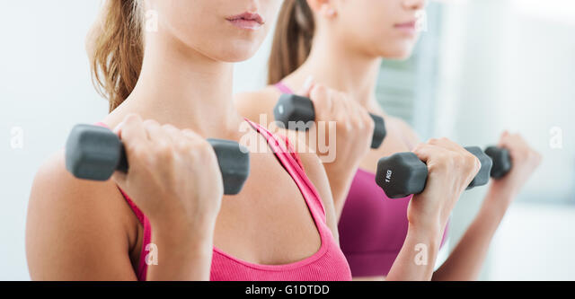 Confident young women exercising and weightlifting at the gym using dumbbells, workout and fitness concept - Stock Image