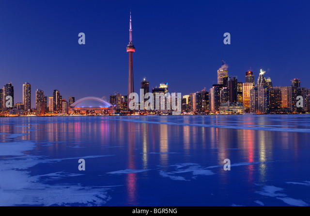 Frozen ice covered Lake Ontario reflecting the lights of Toronto city skyline at dusk in winter - Stock Image