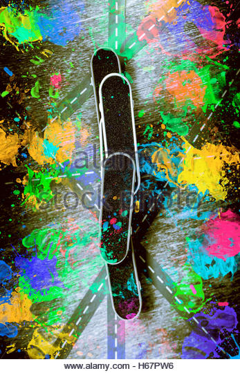 Colourful street sport artwork on trickster skateboard desks balancing on the symmetry of urban sprawl. Skating - Stock Image
