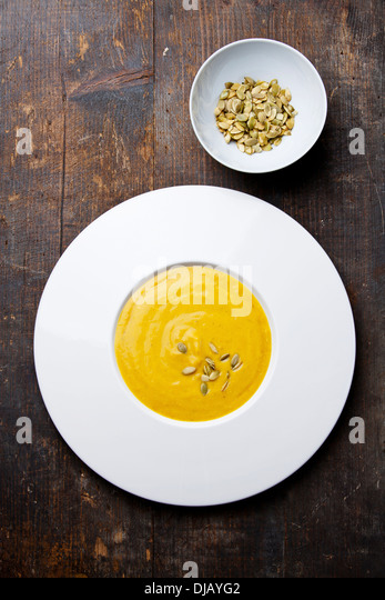 Pumpkin soup with pumpkin Seeds on wooden background - Stock Image