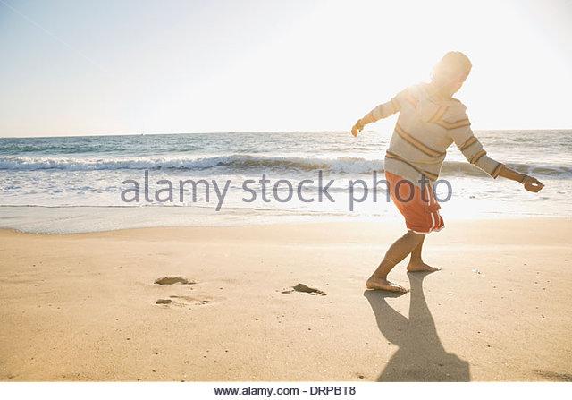 Man throwing shells in ocean - Stock Image