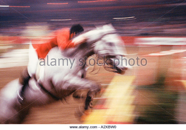 Motion impression image of male rider on gray horse clearing jump in show jumping event. - Stock Image