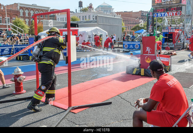 A firefighter completing a timed event with a fire hose. - Stock Image