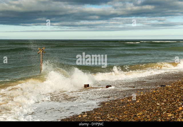 WAVES SMASHING ONTO A GROYNE FINDHORN BEACH MORAY SCOTLAND - Stock Image