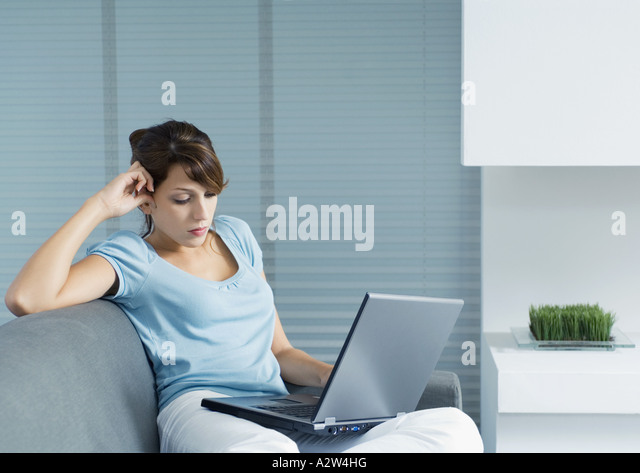 Young woman sitting on sofa, using laptop - Stock Image