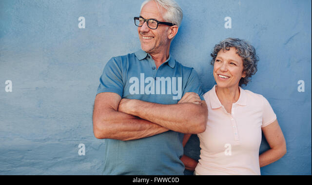 Portrait of a mature couple standing together and looking away and smiling against blue background. Middle aged - Stock Image