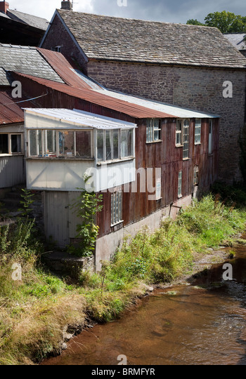 Iron sheet clad extension to building beside river Talgarth Wales UK - Stock Image