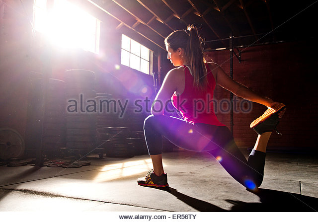 A woman athlete stretches in a crossfit gym. - Stock Image