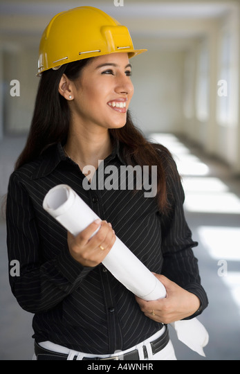 Businesswoman in a hard hat carrying blueprints - Stock-Bilder
