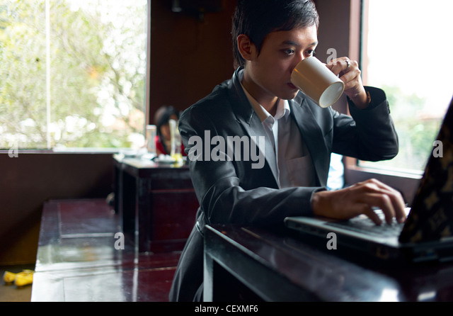 A young businessman drinks coffee while working on his laptop in a cafe in Hanoi, Vietnam - Stock Image