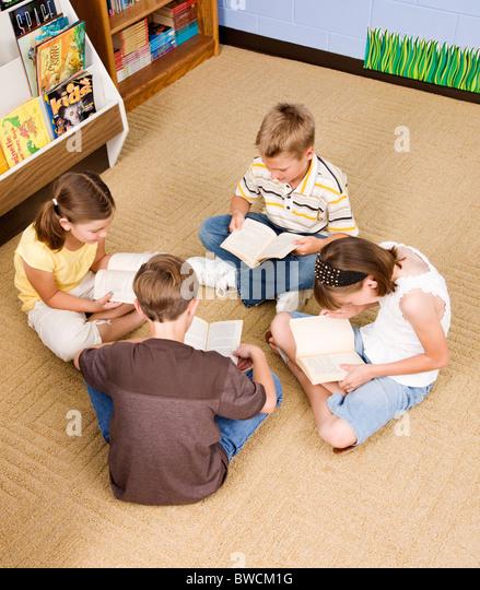 USA, Illinois, Metamora, School children (8-9) reading on floor in school - Stock Image