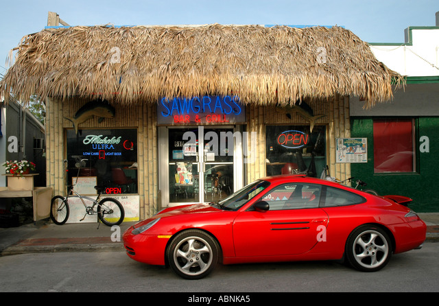 Tarpon Springs Florida Red sports car outside thatch bar - Stock Image