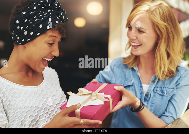 Pretty young blond woman giving an attractive young African American friend a surprise gift gift-wrapped with red - Stock Image