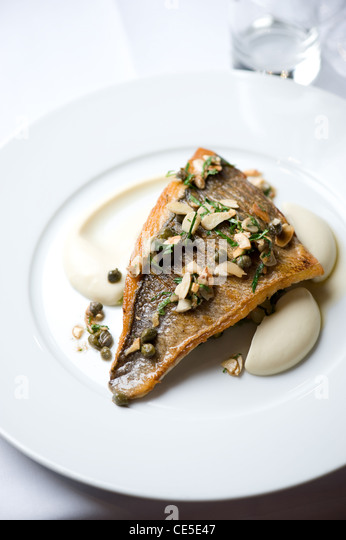 Fish and almonds on a plate - Stock Image