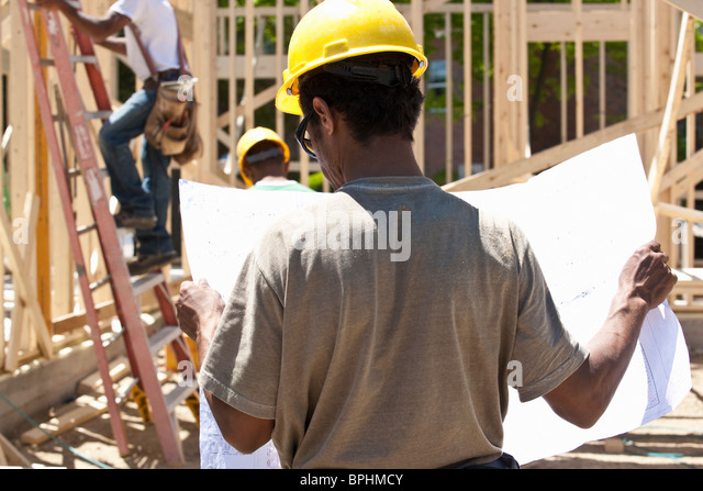 Construction manager reading a blueprint - Stock Image