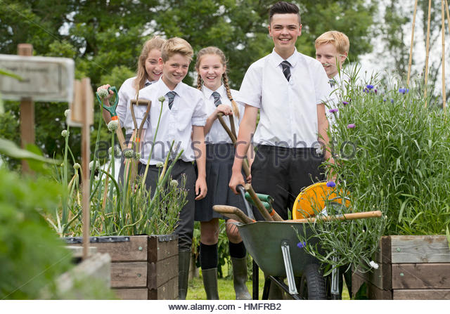 Middle school students with wheelbarrow learning gardening in vegetable garden - Stock-Bilder