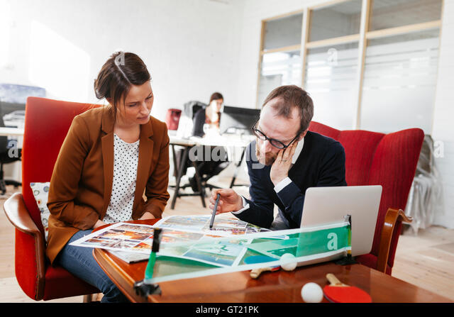 Business colleague discussing while sitting at table in office - Stock-Bilder