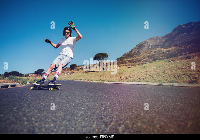 Young man longboarding on a road. Young guy wearing protective gear skating on rural road. - Stock Image