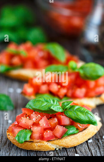 Tomato bruschetta with chopped tomatoes and basil on toasted bread - Stock Image