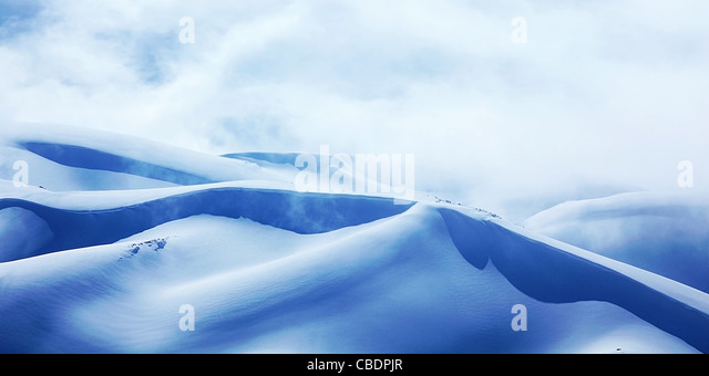 Winter landscape of high mountains with snow blizzard and fresh blue sky, beautiful nature panoramic image - Stock Image