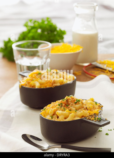Two servings of baked macaroni and cheese with parsley garnish, a bowl of cheese and a glass of milk in the background. - Stock Image