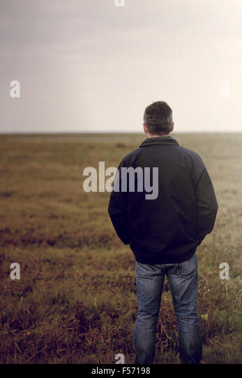 Handsome middle aged man walking through a rural coastal area - Stock Image