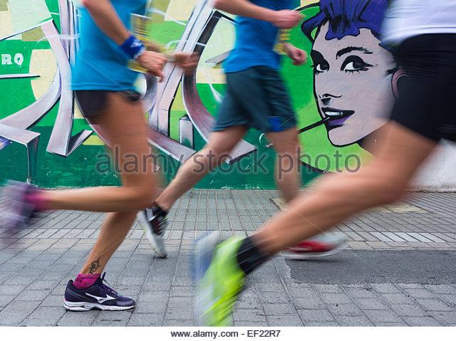 Runners running past Audrey Hepburn graffiti during City marathon - Stock-Bilder