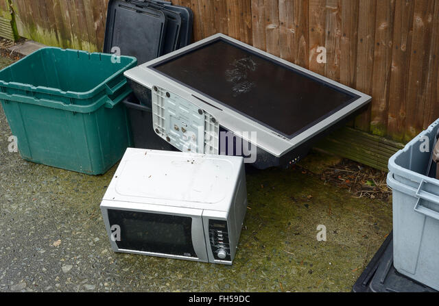 An old TV and microwave oven dumped on a pavement - Stock Image
