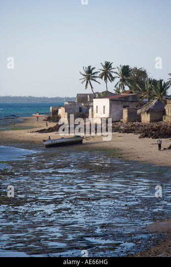 Houses from the reed town line the shore of the southern end of Ilha do Mozambique at low tide - Stock Image