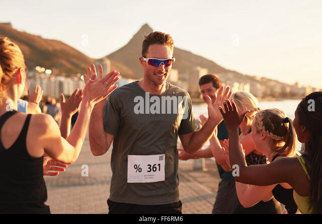 Group of young adults cheering and high fiving a male athlete crossing finish line. Sportsman giving high five to - Stock Image