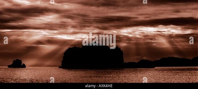 sunlight streak through clouds break apard separate contrast black pink red white yellow nature rocks island - Stock Image