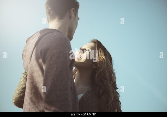 Romantic young teenagers staring at each other against blue sky, love and relationships concept - Stock Image