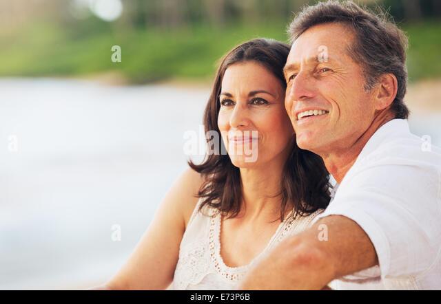 Happy Romantic Mature Couple Enjoying Sunset on the Beach - Stock Image