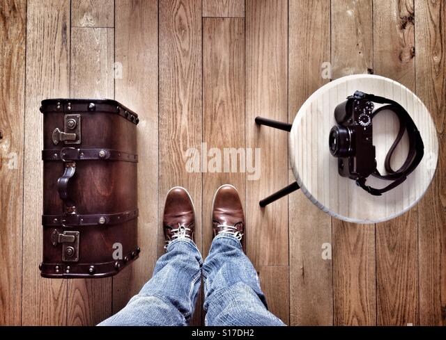 Man standing on a wooden floor next to him an Old suitcase and a photo camera - Stock-Bilder