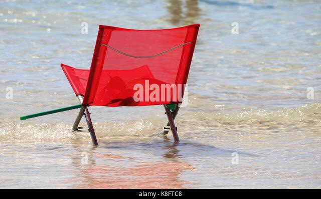 A red beach chair in the water - Stock Image