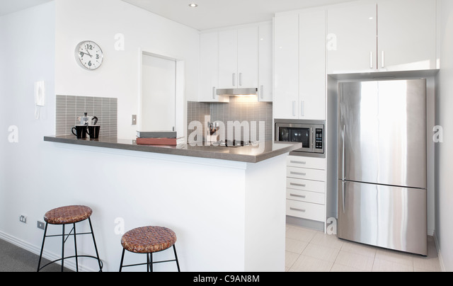 Modern white Kitchen in apartment with Polished Stainless Steel Appliances - Stock Image