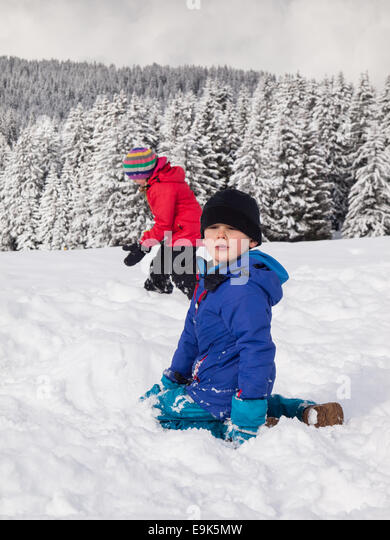 small boy  playing in the snow with small girl and wooded winter  mountain landscape behind - Stock Image
