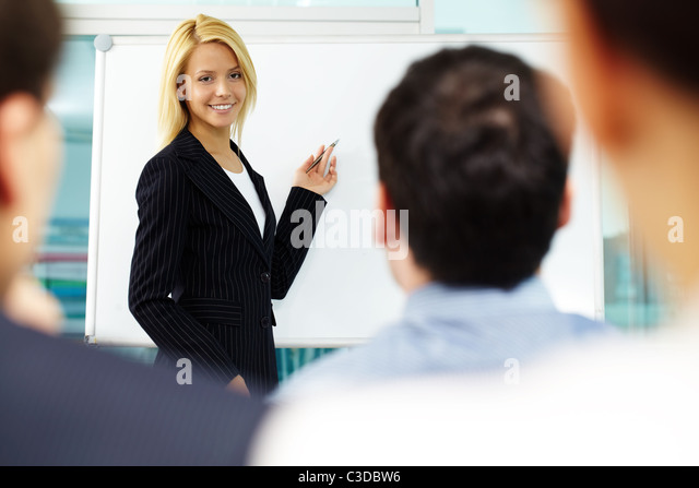 Pretty manager pointing at whiteboard while colleagues listening to her - Stock Image