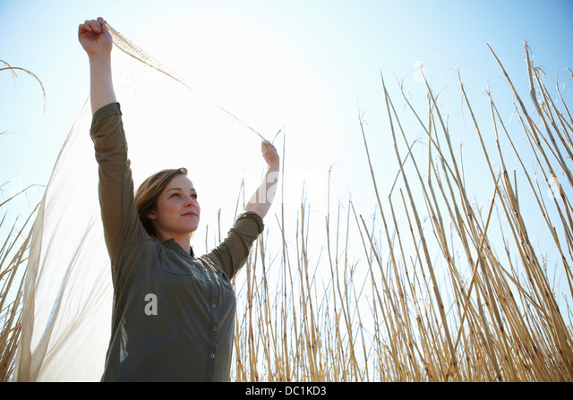 Young woman holding up scarf in reeds - Stock Image