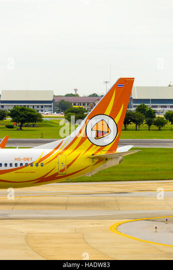 A golf course and golfers visible behind the tail section and logo of low cost carrier, Nok Air airplane taxiing - Stock Image