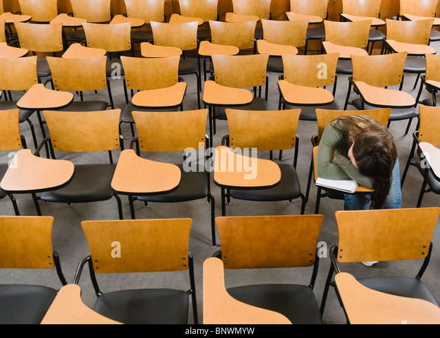 College student sleeping in empty lecture hall - Stock Image