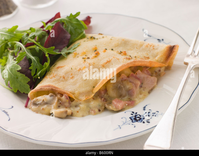 Savoury Pancake filled with Ham Cheese and Mushrooms with dressed salad - Stock Image