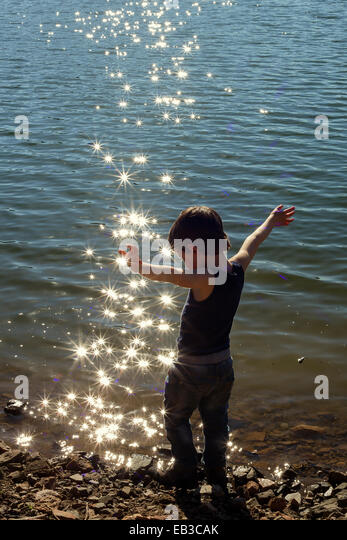 Boy standing at water's edge with arms outstretched - Stock Image